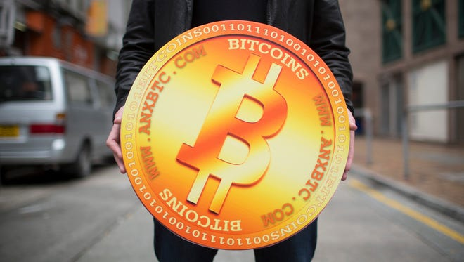 A man poses for a photograph with a mock Bitcoin.