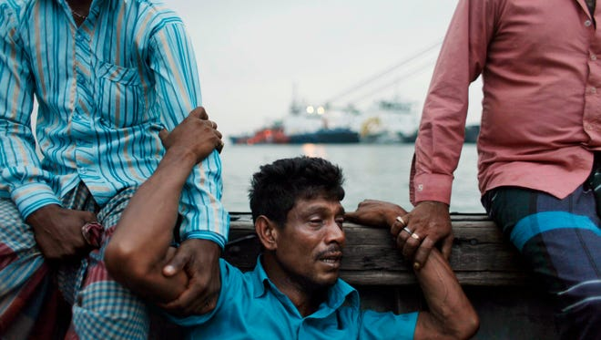 A Bangladeshi man mourns for his missing brother, as rescuers continue to search the site of a ferry that sank on the banks of the River Meghna in Bangladesh.