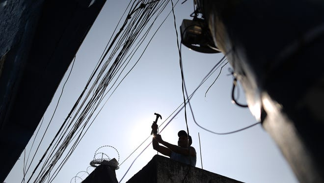 FILE - In this July 2, 2014 file photo, a man works on the rooftop of a home at the Providencia slum of Rio de Janeiro, Brazil.