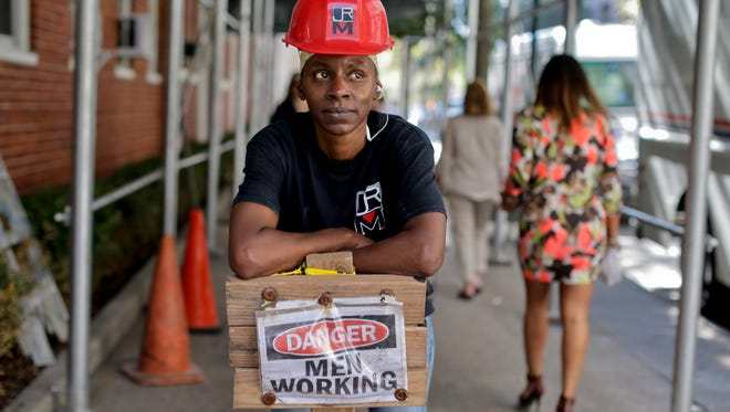 In this Aug. 14, 2014 photo, Sophia McIntosh stands for a photo outside a construction site where she works as a shop steward, in New York.