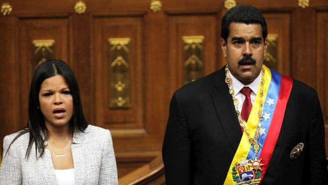 In this April 19, 2013 file photo, daughter of the late Hugo Chavez, Maria Gabriela Chavez and Venezuela's newly sworn-in President Nicolas Maduro, join in the singing of their national anthem in the National Assembly, in Caracas, Venezuela.