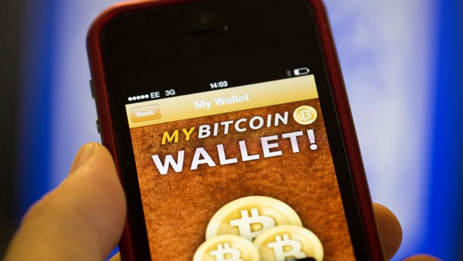 An Apple Inc. iPhone5 displays the Bitcoin Wallet smartphone app in this arranged photograph at the Pembury Tavern in London, U.K., on Wednesday, Oct. 9, 2013.