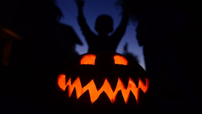 Children play behind a pumpkin carved and lit for Halloween on Oct. 30 in Monterey Park, Calif.