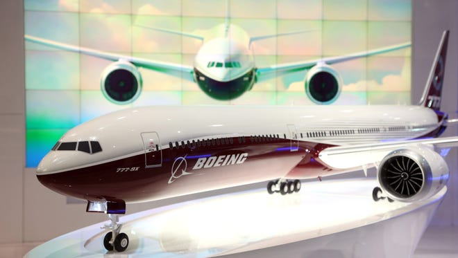 A model of Boeing's 777X aircraft, manufactured by Boeing Co., sits in front of a picture display for the new aircraft on the company's stand during the 13th Dubai Airshow at Dubai World Central (DWC) in Dubai, United Arab Emirates, on Monday, Nov. 18, 2013.