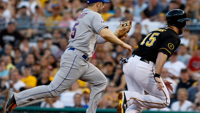 The Pittsburgh Pirates' Ike Davis, right, heads for first base as Mets third baseman David Wright reaches to tag him in a rundown between first and second in the fourth inning Thursday in Pittsburgh. Andrew McCutchen scored from third on the play before Davis was tagged for the third out.