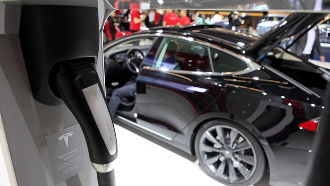 An electric charging plug for a Tesla automobile sits in a docking station beside a Tesla Model S automobile, produced by Tesla Motors Inc., at the 65th Frankfurt International Motor Show in Frankfurt, Germany, on Wednesday, Sept. 11, 2013. The 65th Frankfurt International Motor Show, Europe's biggest auto event, will open to the public on Sept. 12 and showcase the industry's latest models. Photographer: Krisztian Bocsi/Bloomberg