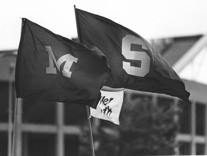The University of Michigan and Michigan State flags