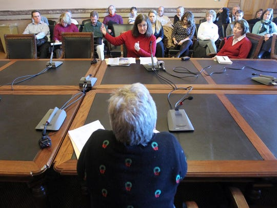 Susan Voss, then the Iowa insurance commissioner, listens to testimony during a 2010 public hearing at the Iowa Capitol building.