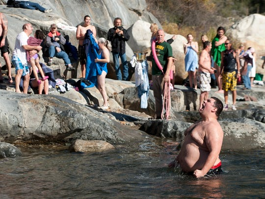Ryan Fansett celebrates the New Year from the chilly Kaweah River during the annual Polar Bear Dip at the Gateway Restaurant in Three Rivers on Thursday.