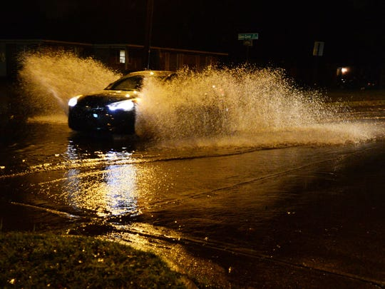 A car makes a big splash as it drives in a flooded
