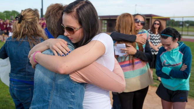 Syndey Wenzel, 15, hugs Nichole Temu of Ankeny during a memorial for her son, Zacharie Schaubhut, Tuesday, June 2, 2015, on the Ankeny High School baseball field in Ankeny.