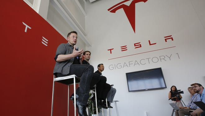 FILE--In this July 26, 2016, file photo, Elon Musk, CEO of Tesla Motors Inc., left, discusses the company's new Gigafactory in Sparks, Nev. Tesla announced Thursday, Sept. 15, 2016, that it had been selected by the utility to construct the battery storage project at the Mira Loma substation in California's Riverside County. (AP Photo/Rich Pedroncelli, file)