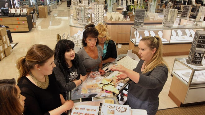 Stacey Hall (right), a sales and marketing coordinator for James Avery Jewelry, shows employees her company's merchandise at the new Dillard's store at Liberty Center.