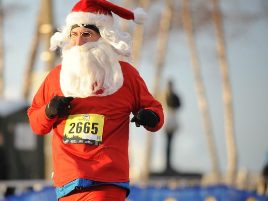 Rick Armes crosses the finish line during the Fifth Third Bank annual Turkey Trot before the parade Thursday
