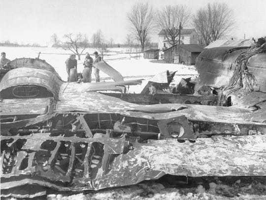 Farmers view the scene of the crash of a Northwest Airlines Electra the day after the jet exploded and crashed.