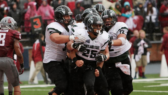 Portland State running back Nate Tago (25) celebrates with teammates, including offensive lineman Chad Bach (72), offensive lineman Kyle Smith, left, after scoring a touchdown during the second half of an NCAA college football game against Washington State, Saturday, Sept. 5, 2015, in Pullman, Wash. Portland State won 24-17.