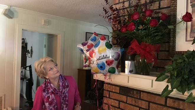 """Carol Lindley looks at flowers, balloons and candy she received as part of her """"winnings"""" from a sweepstakes which turned out to be a scam."""