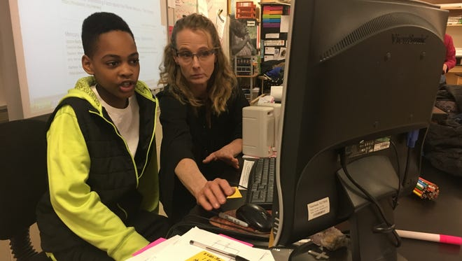 Southside science teacher Deborah Kirkman works with sixth grader Robert Coleman on his solar system project. Coleman is one of 10 students for whom Kirkman volunteers her time to work with at least once a week.