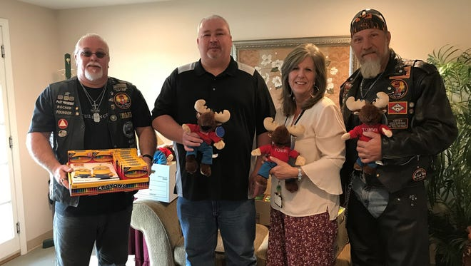 """Representatives from the Mountain Home Moose Lodge #1953 and the Moose Riders recently donated toys and coloring books to Serenity, Inc., for children staying in the facility's shelter. Pictured are: (from left) Jeffrey Shaddy, David Albrecht, SerenityDirector Donna Forrester and Richie Yanke. """"We are so grateful for all the support the Lodge has given us,"""" Serenity said in news release."""