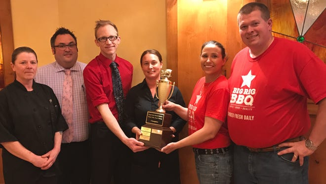 Grille 26 staff receive the 2017 Argus Leader Food Falls Restaurant championship trophy from 2016 winners Big Rig BBQ. From left: Grille 26 cook Judy Oleson, owner Tim Meagher, manager Clifton Curry and server Bobby Jo Hostetler and Big Rig BBQ owners Nichole and Bob Brenner.