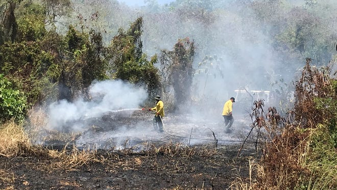 John Perez with Leroy Paulino extinguishes the remainder of the flames from the grass fire.  Talofofo Fire Department Sunday afternoon respond to along the cliff-side of Talofofo Bay.