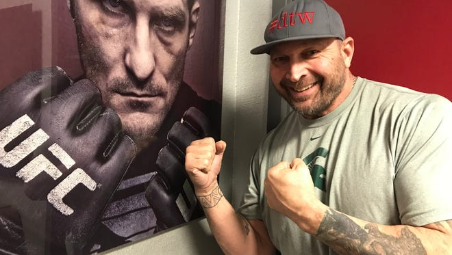Former Michigan State star and No. 2 pick in the 1989 NFL Draft, Tony Mandarich, stands in front of one of his photos inside his studio in Scottsdale, Arizona last December.
