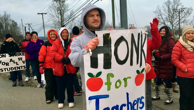 Striking teachers wave at passing cars outside Poca High School, Feb. 19, 2019, in Poca, W.Va.  Poca is in Putnam County, the only county in the state where public schools were held on the first day of a statewide teachers strike.