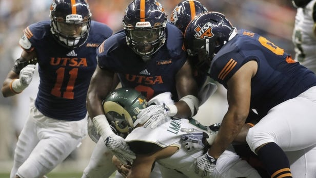 Colorado State Rams running back Izzy Matthews (35) is stopped by University of Texas-San Antonio Roadrunners defenders Nate Gaines (11), Michael Edwuagu (8) and Brian Price (91) during a Sept. 26, 2015 game at the Alamodome.