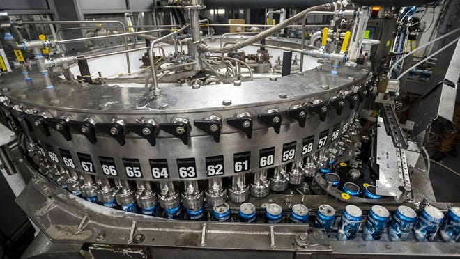 Cans are filled with Wachusett Blueberry along the line at Wachusett Brewery in April 2019.  In response to the pandemic, breweries quickly shifted sales from on-premise draft pours to off-premise sales, and that has created a new problem: a shortage of can.