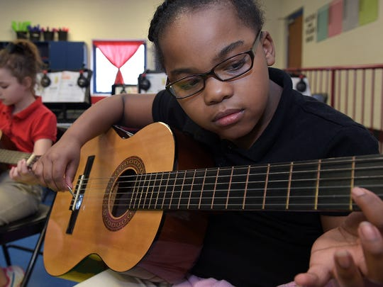 Brielle Walker learns to play the guitar during an after-school class at Cumberland Elementary School.