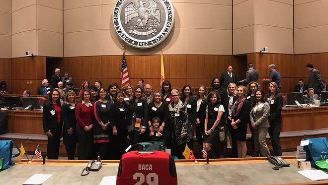 """Recipients of the """"New Mexico Family Friendly Business Award"""" from around the state pose on the Senate floor in Santa Fe after receiving their award. Jamie Wagoner, a benefits and compensation manager for the city of Farmington, is in the front row, second from right."""