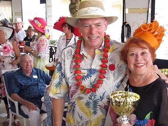 MIYC Chairman Dave Everitt congratulates Corinne Margulies, winner of the Most Creative Fascinator trophy.