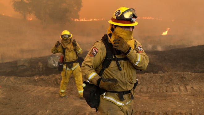 Firefighters with Cal Fire Mendocino Unit protect themselves from smoke and ash created by an advancing wildfire on July 30, 2018, in Lakeport, Calif.