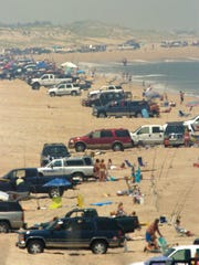 Surf fishermen line the beach with their vehicles at