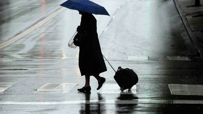 A pedestrian walks across Fifth Avenue North at Charlotte Avenue in downtown Nashville during a rain storm Wednesday morning April 24, 2013.