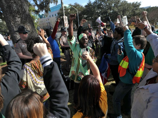 Cameron Montgomery, center, raises a fist with counter-protests,