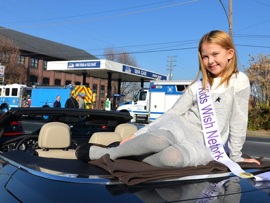 Savannah Kennedy, 9, Lebanon, poses on top of the convertible