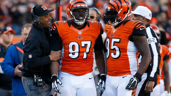 The Cincinnati Bengals defensive tackle Geno Atkins (97) is congratulated by the head coach Marvin Lewis and defensive end Wallace Gilberry (95) after chasing down the Jacksonville Jaguars quarterback Blake Bortles (5) and making the tackle in the second half at Paul Brown Stadium.  The Enquirer/Jeff Swinger