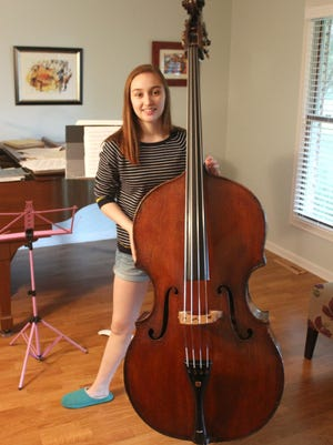 Nina Bernat, 15, stands with her father's bass at her home in Iowa City.