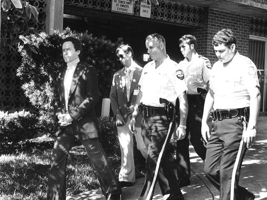 Ted Bundy, left, with Leon County Sheriff's officers in this undated file photo.