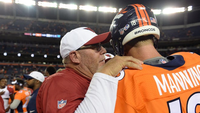 Arizona Cardinals head coach Bruce Arians and Denver Broncos quarterback Peyton Manning (18) following a preseason game at Sports Authority Field at Mile High in Denver.