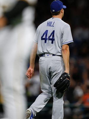 Los Angeles Dodgers starting pitcher Rich Hill walks off the mound after Pittsburgh Pirates' Josh Harrison hit a solo home run to win the game and break up Hill's no-hit effort in the 10th inning. The Pirates won 1-0.
