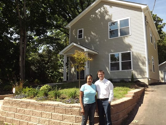 Vearon Poyser-Smith and the Rev. Jeremy Montgomery in front of Poyser-Smith's new home in Plainfield.