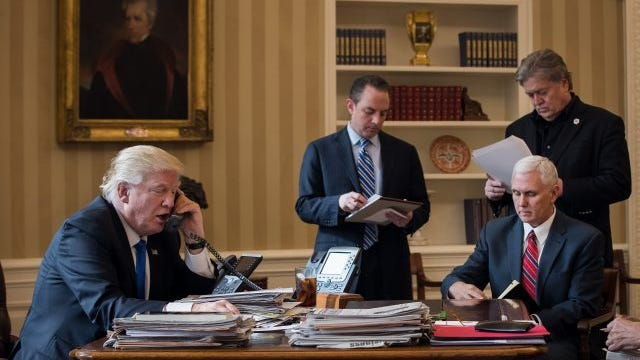President Donald Trump speaks on the phone with Russian President Vladimir Putin in the Oval Office of the White House, January 28, 2017 in Washington, DC. Also pictured, from left, White House Chief of Staff Reince Priebus, Vice President Mike Pence and White House Chief Strategist Steve Bannon.