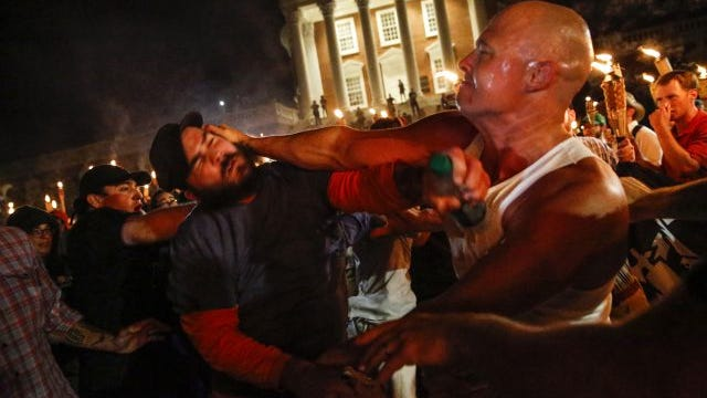 White nationalist groups, a member pictured on right, feud with counter protesters on the UVA campus in Charlottesville on Friday, August 11, 2017. The nationalists marched with torches through the campus.