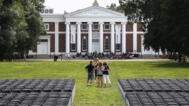 A family takes photographs during first year move-in day while on the Lawn of the University of Virginia, Friday, Aug. 18, 2017, in Charlottesville, Va., a week after a white nationalist rally took place on the campus.