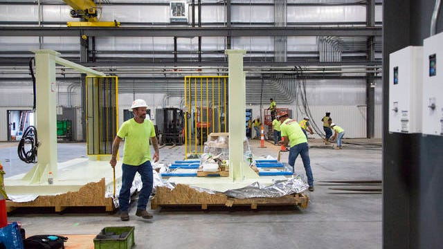 Workers install blow molding and fuel tank assembly equipment at the Fuel Total Systems plant at the Cherry Glen Industrial Park in Mt. Pleasant on Tuesday, Aug. 20, 2019.