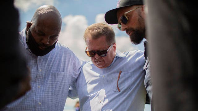 Spring Hill Mayor Rick Graham prays with Commission Keith Hudson, left, and Pastor Mark Rampulla SouthView Church during a Black Lives Matter demonstration held at the intersection of Main Street and Campbell Station Parkway in Spring Hill, Tenn., on Tuesday, June 2, 2020.