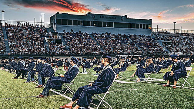 Bartlesville High School graduates sit beneath the sunset as friends and family watch the ceremony for the Class of 2020 last July at Custer Stadium. Examiner-Enterprise file
