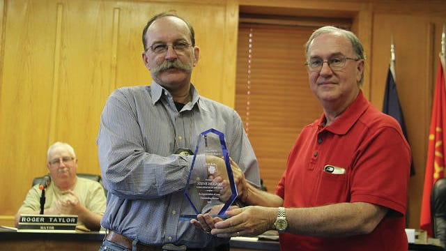 Larry Eulert, at right, is shown here as he congratulates Pawhuska code enforcement officer Steve Hughes, left, on receiving an award from the state association of code enforcement officers. Eulert took an interest in the cleaning up of blighted properties in the city. Robert Smith/Journal-Capital